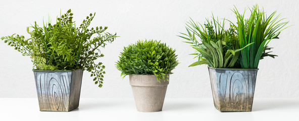 Variety of artificial houseplants against grey wall, crop