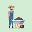 gardener man pushing wheelbarrow full of earth compost male farmer working in garden wearing overalls gardening concept full length