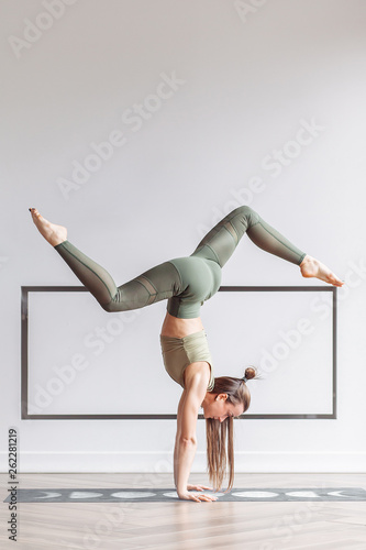 Fotografia Beautiful young fitness model doing a difficult handstand in the gym