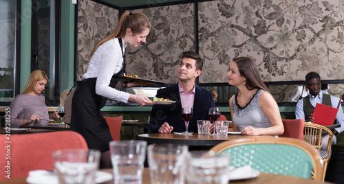 Waitress bringing dishes to couple Fototapet