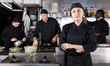 canvas print picture Confident female chef with a team of cooks in restaurant kitchen