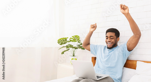 Young happy black guy celebrating success in bed Canvas-taulu