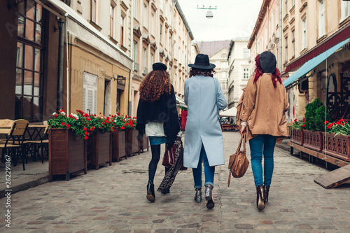 obraz PCV Outdoor shot of three young women walking on city street. Girls having fun. Back view