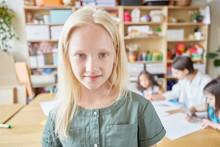 Lovely Albino Girl Smiling And Looking At Camera While Standing On Blurred Background Of Classroom In Art School