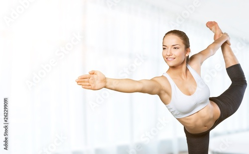 Fototapeta  Young beautiful woman doing Yoga on white background