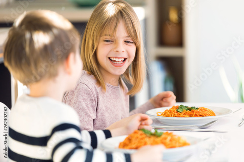 Fotografía Smiling children having fun while eating spaghetti with tomato sauce in the kitchen at home