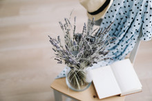 Creative Flat Lay Top View. Blue Dress, Sun Hat, Flowers In A Vase And A Book On Wooden  Background. Summer Holiday Concept.