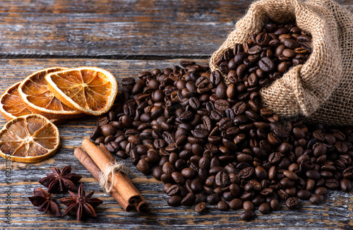 Coffee beans fragrant aromatic in a canvas bag on a wooden table. Morning coffee concept.