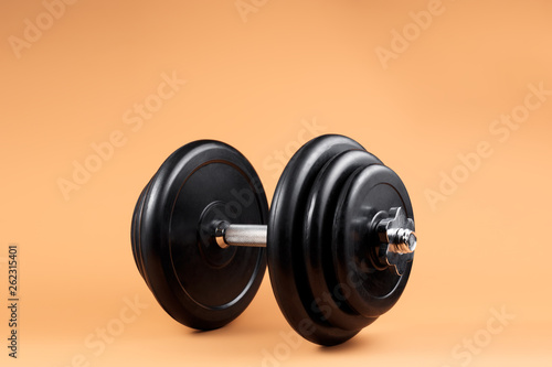 Fototapeta Professional dumbbell and weight plates over beige background. Black metal dumbbell with chrome silver handle. Gym equipment. Fitness concept. obraz