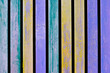 Colorful blue, yellow and turquoise wooden aged plank wall.