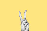 Concept of peace, pacifism, hippie, love. Hand making the two fingers peace sign. Black and white subject with yellow background - 262334472