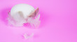 Leinwanddruck Bild -  White egg on white feathers on a pink background, selective focus