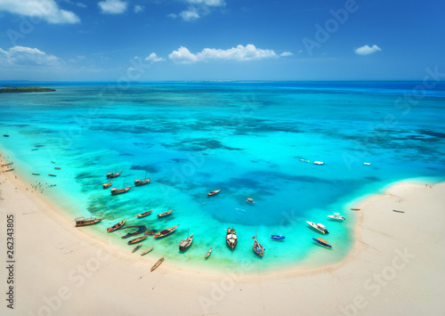 Foto auf Leinwand Sansibar Aerial view of the fishing boats on tropical sea coast with sandy beach at sunny day. Summer holiday. Indian Ocean, Zanzibar, Africa. Landscape with boat, white sand, azure water, blue sky. Top view
