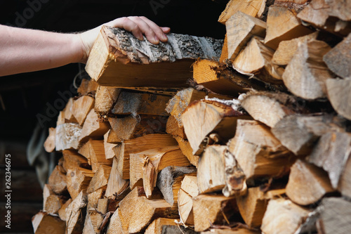 A man's hand takes a birch dry chipped log from a woodpile.