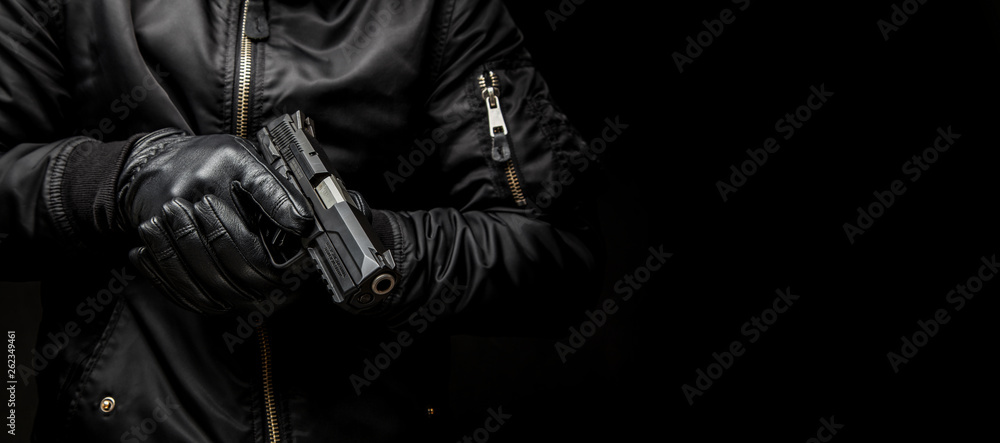 Fototapeta a man in a black jacket and black gloves holding a gun on a dark back
