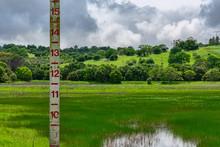 Water Level Gauge Indicator Monitor The Flood Water In Dam, Lake On Rainy Day. Nimbostratus Rain Cloud. Green Basin Of  Lake, Dam.