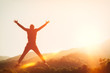 Happy man jumping at top of mountain with sunset sky abstract background.