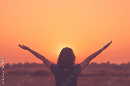Fototapeta Freedom feel good and summer vacation adventure concept. Copy space of woman raise hand up standing at rice field and morning sky abstract background. obraz na płótnie