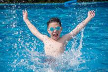 Happy Asian Boy Having Fun Splashing In Swimming Pool