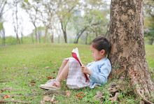 Portrait Little Asian Child Girl Reading Book In Park Outdoor Sitting Lean Against Tree Trunk In The Garden Outdoor.
