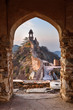 Leinwanddruck Bild - Ancient long wall with towers around Amber Fort through the arch of tower walls at morning. Rajasthan. India