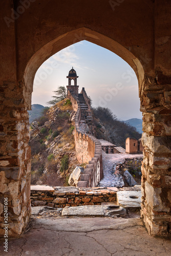 Pinturas sobre lienzo  Ancient long wall with towers around Amber Fort through the arch of tower walls at morning