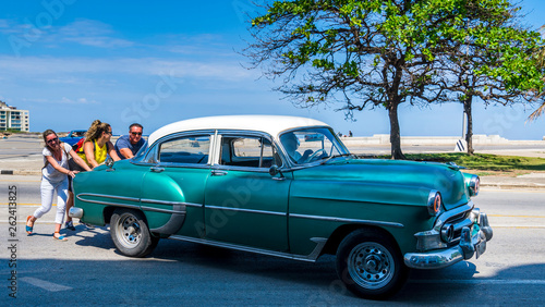 Cuba, Havana: Old American classic car cab, broke down, tourists are pushing the car away from the street Wallpaper Mural