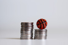 Two Pile Of Coins And A Miniature Basketball.