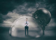 canvas print picture - Businessman safely inside a shield dome during a storm that protects him from a wrecking ball. Protection and safety concept