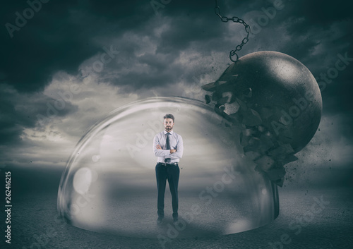 Fényképezés Businessman safely inside a shield dome during a storm that protects him from a wrecking ball