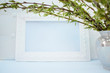 White frame with branches of green willow on a blue background. Copy space in the middle for your text.