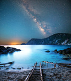 Fototapeta Natura - fascinating mystical magical landscape with a deach and boat racks at night in the light of the Milky Way stars