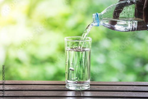 Fototapeta Drink water pouring into glass on wooden table over sunlight with natural lighting and background obraz na płótnie