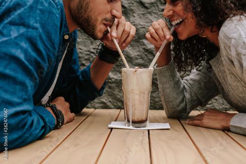 Obraz na plátne Loving couple sharing milkshake