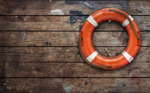 Lifebuoy On Rough Wooden Wall....
