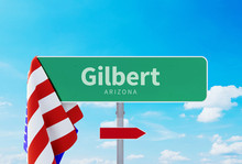 Gilbert - Arizona. Road Or Town Sign. Flag Of The United States. Blue Sky. Red Arrow Shows The Direction In The City