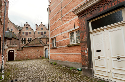 Closed door of brick wall home of historical Beguinage, 13th century complex hou Canvas Print