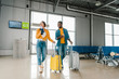 smiling african american couple walking together in airport with travel bags