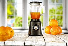 Black Blender On White Wooden Table In Kitchen With Window And Fresh Orange Fruits. Free Space For Your Decoration.