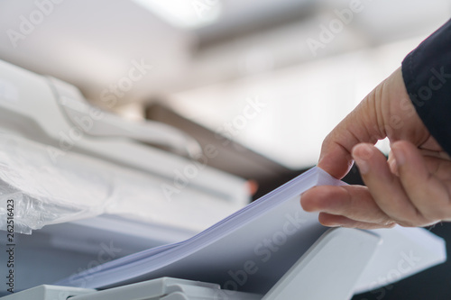 mata magnetyczna Business printer / printing documents in office concept: Businessman press white paper in laser printed cartridge feeder, scanner machine for copy document to report in busy modern offices background