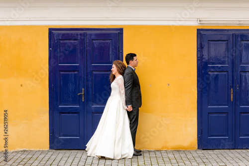 Photo  Beautiful wedding couple posing in city in front of old blue door