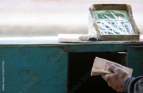 A Tunisian illegal black market money changer clutches a