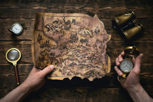 Old Map In Man Adventurer Hands On A Brown Table Background. Treasure Hunt Concept.