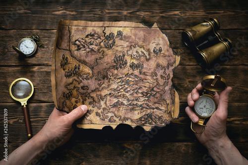 Fotografia Old map in man adventurer hands on a brown table background