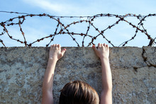 A Young Street Child Climbs On A Fence With A Loops Of Rusty Barbed Wire Against A Blue Sky