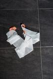 Bandage gauze with tape lying on grey tile floor. Top view. - 262568082