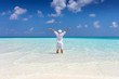 Man in white summer clothes stands on a tropical beach with turquoise sea and enjoys his freedom