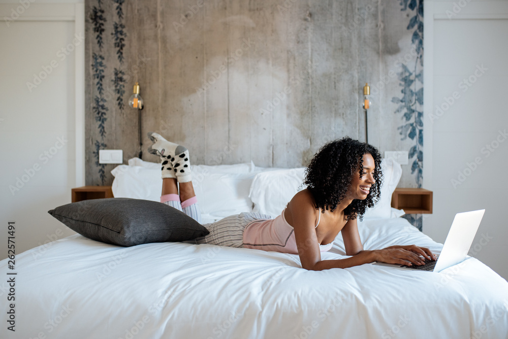 Fototapety, obrazy: Woman sitting on bed on the computer