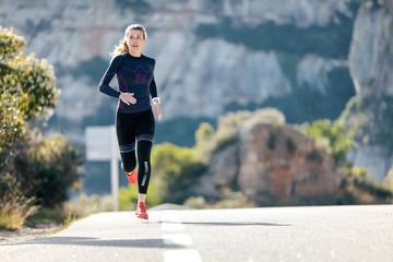 Sportska mlada žena koja trči planinskom cestom u prekrasnoj prirodi.