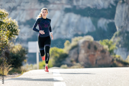 Sporty young woman running on mountain road in beautiful nature. Fototapete